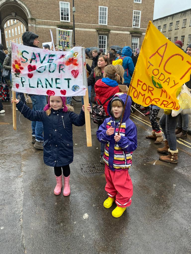 "Two young children holding environmental signs saying ""Save Our Planet"" and ""Act Today for my Tomorrow"""